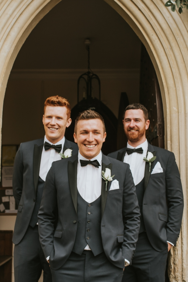 Groom and groomsmen laugh outside the church