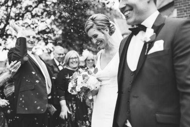 Bride and groom walk through a confetti shower
