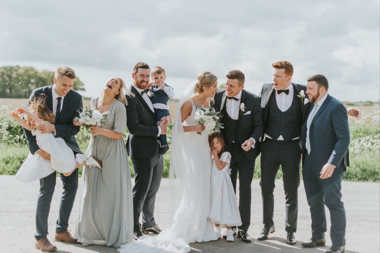 Bridal party laugh during a group photo