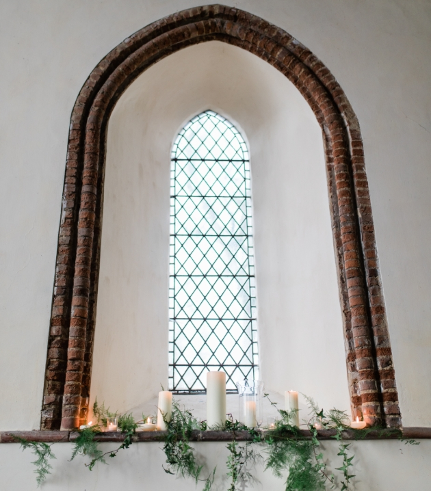 Church window dressed with candles and greenery