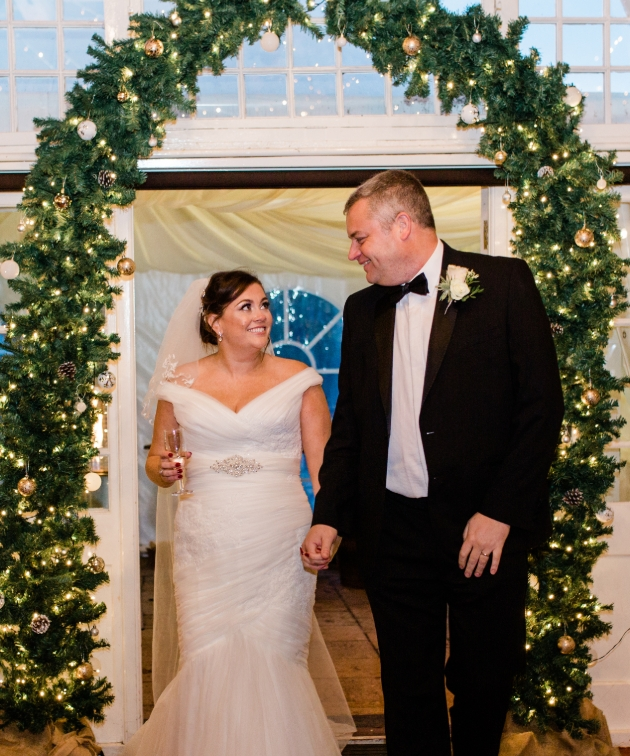 Bride and groom enter the wedding breakfast through an illuminated festive arch