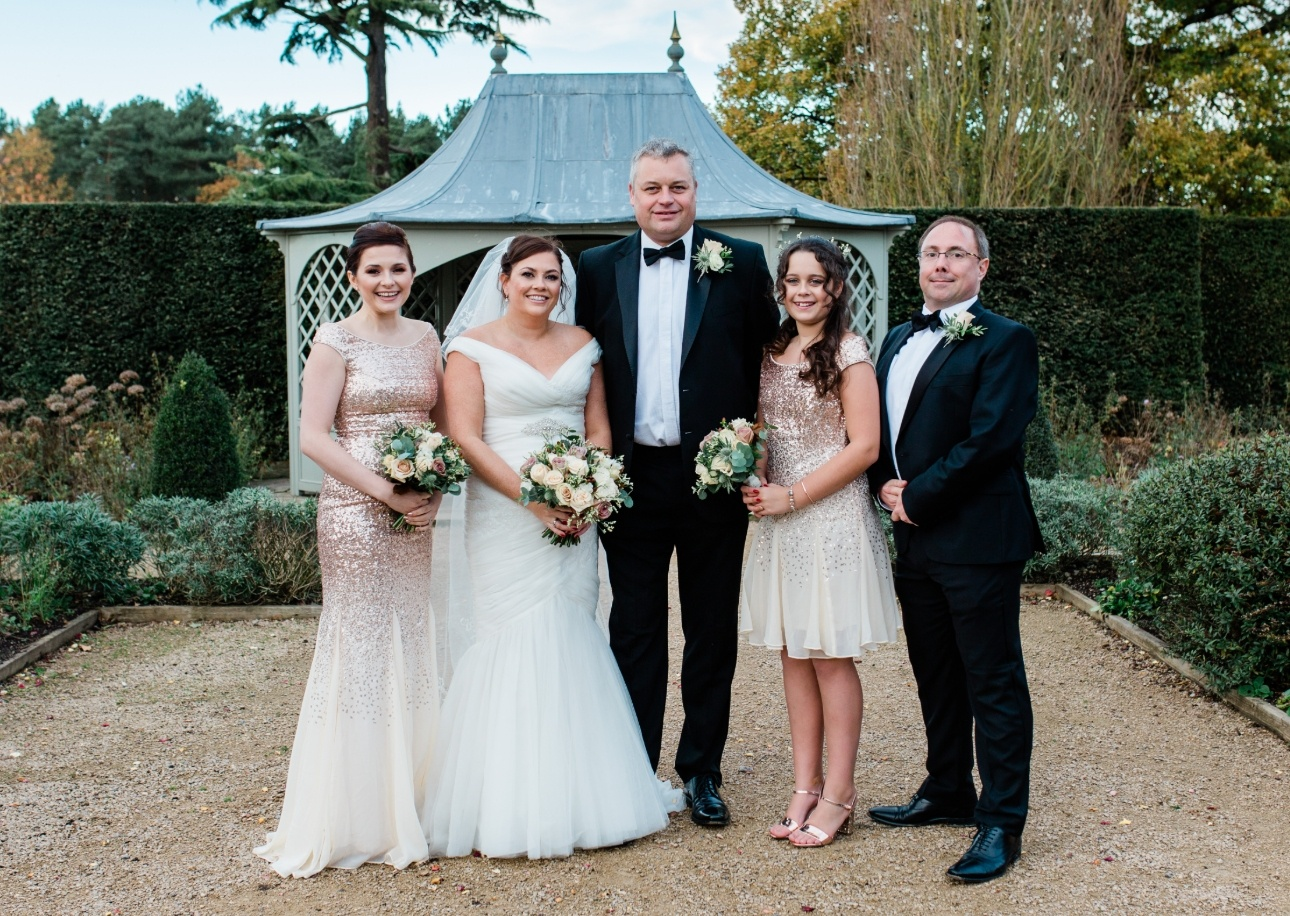 The men dressed in black-tie dinner suits with bridesmaids in gold sparkly dresses