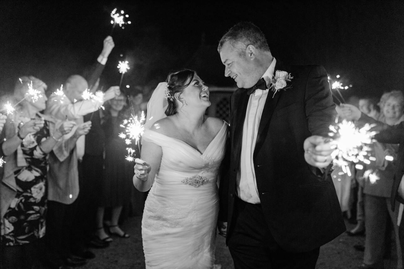 Bride and groom smile with sparklers in front of their wedding guests
