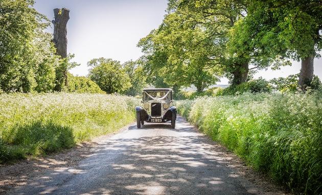 vintage car driving down country lane
