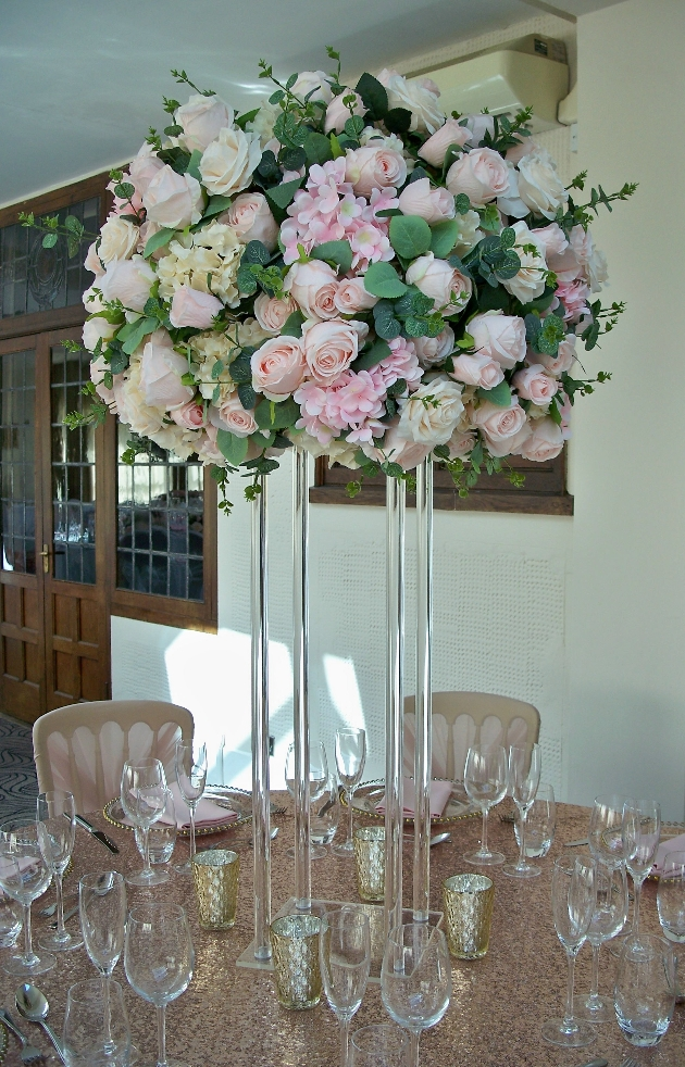 high centrepiece with blush floral display on sequin cloth