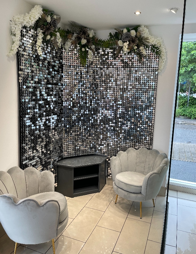 grey suede chairs in front of disco ball wall