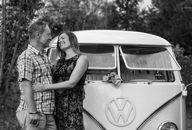 couple standing in front of retro campervan