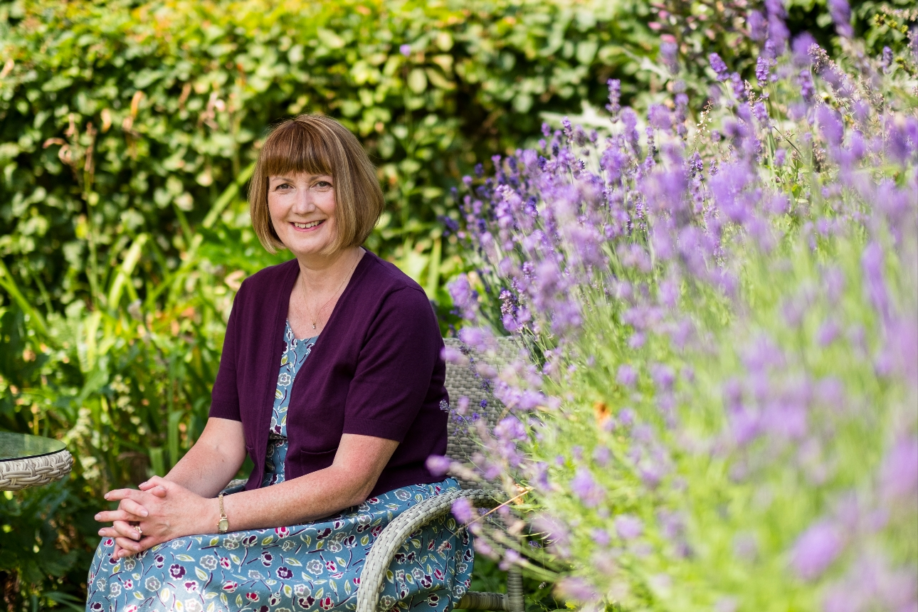 lady sat on a garden chair next to a border of lavender