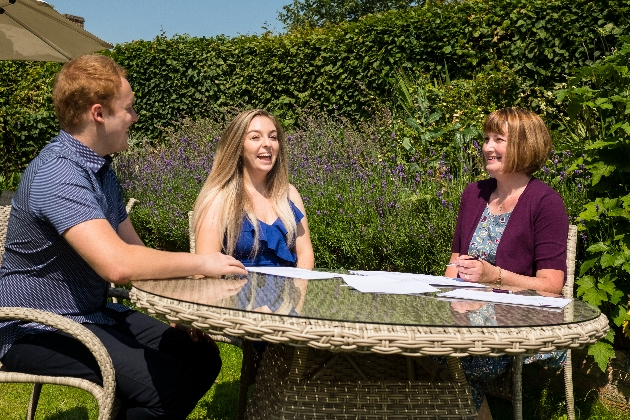 woman sat with a couple at garden table