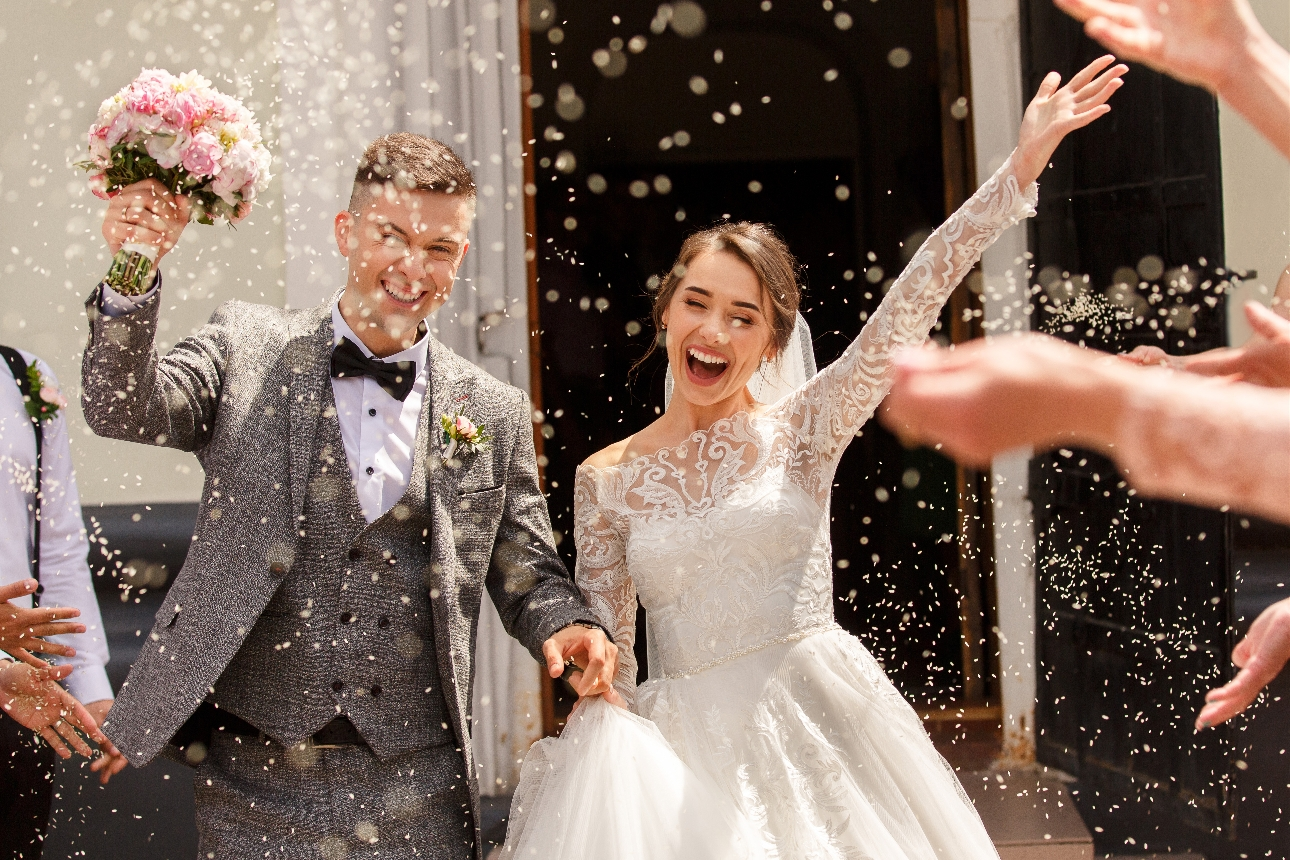 bride and groom leaving church under a shower of confetti