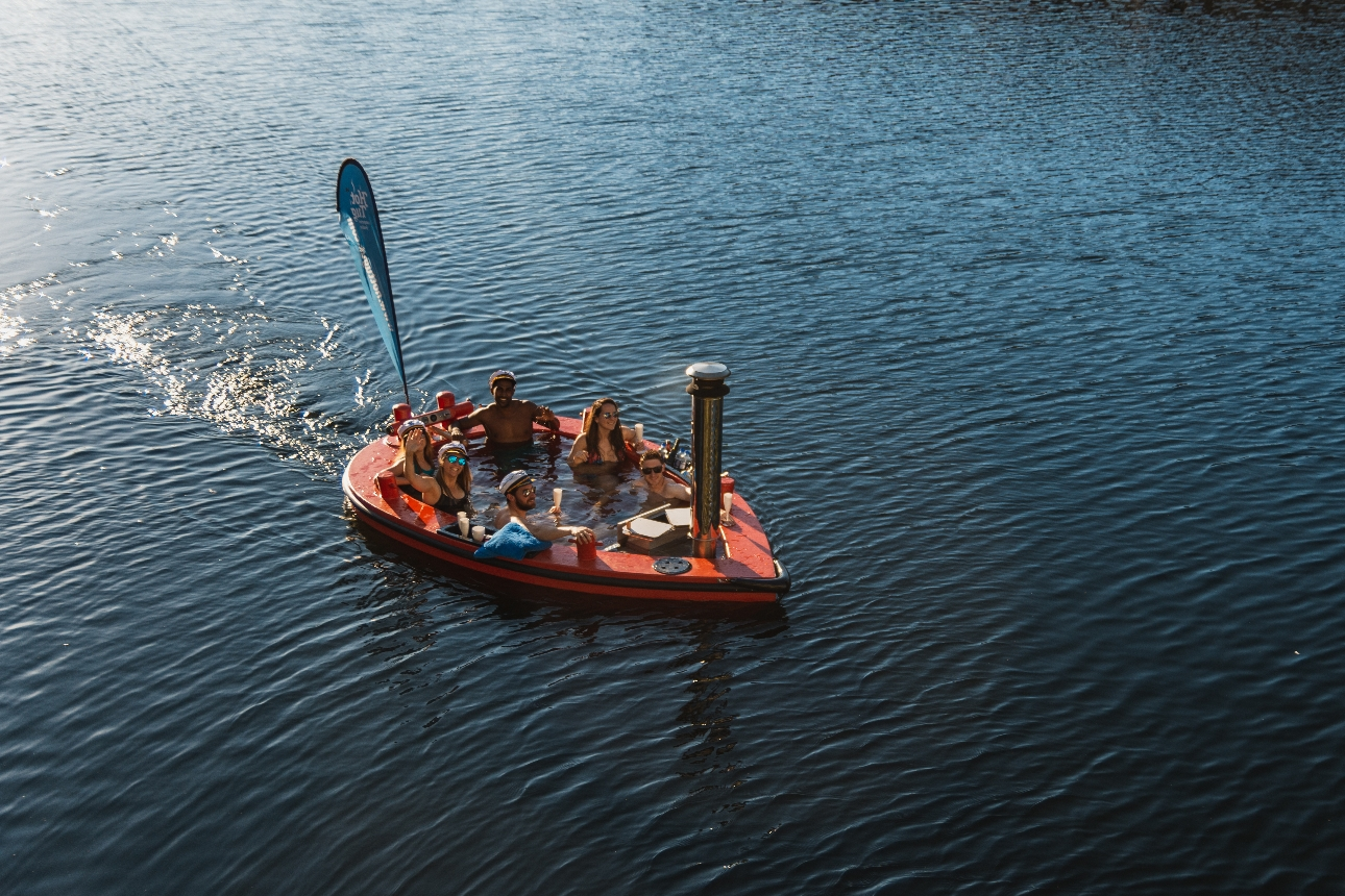 men and women in a hot tub boat on a lake