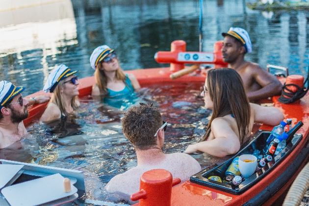 group of men and women in a floating hot tub down a river