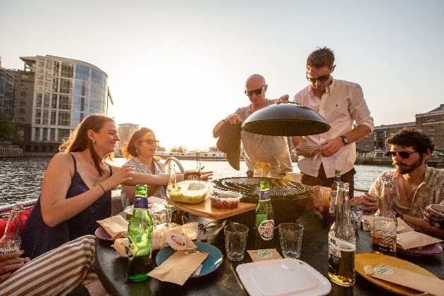 group on a floating boat with a barbecue down a river